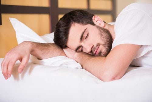 man sleeping restfully in bed