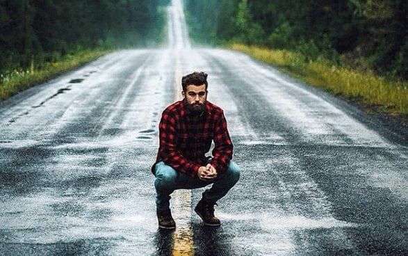 lumbersexual look man in red flannel shirt jeans