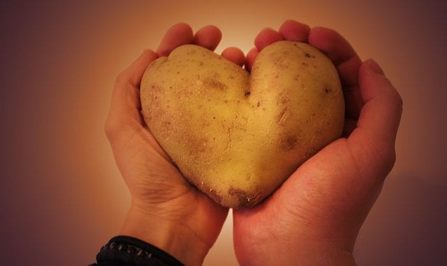 man and woman holding a heart shaped potato