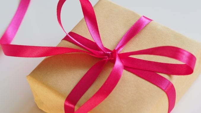 a brown box gift wraped with a red tape