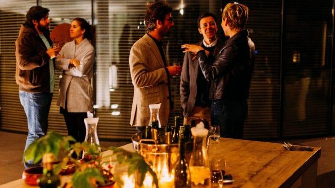 5 people speaking at dinner