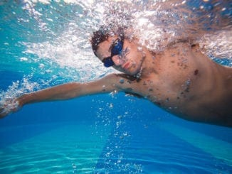 man swimming underwater athletic