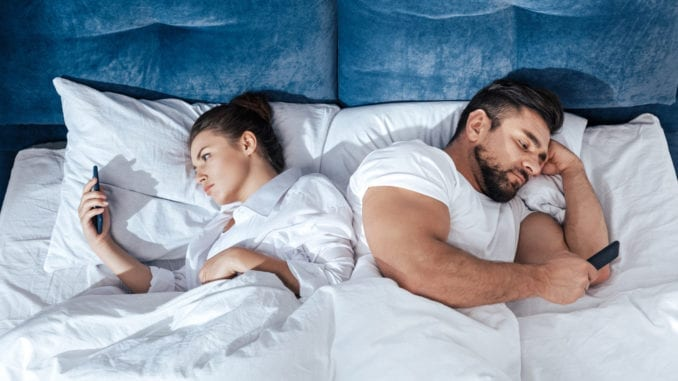 couple on smartphones in bed reading digital information