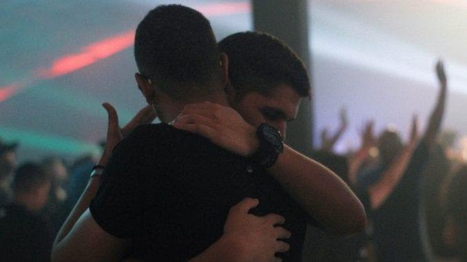 holding hugging men